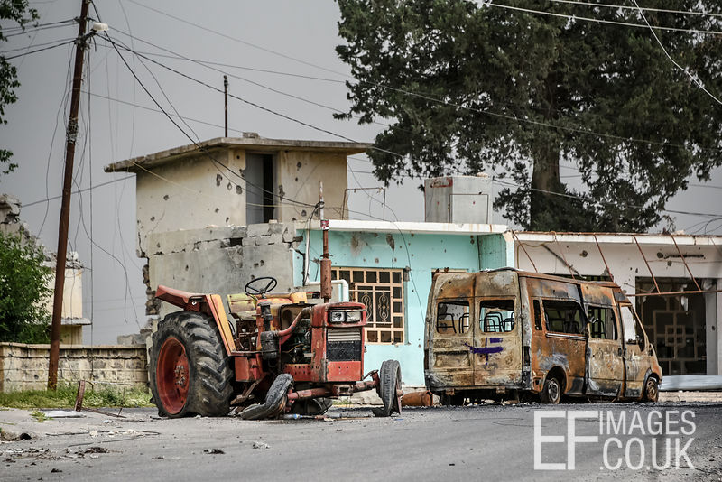 A burned out tractor and van abandoned in front of a bullet riddled home on the streets of Badush during its liberation from ISIS by the Iraqi Army. 1st May 2017