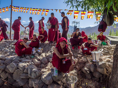 A group of monks chat while they take some time out from serving tea to the crowd.