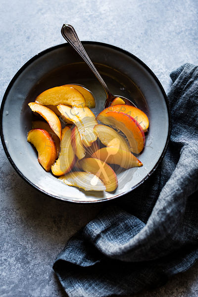 Sliced peaches in a bowl with spoon and napkin