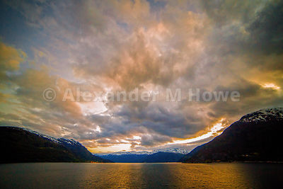 Magnifiecent  Clouds over a Golden Orange Fjord in Early Morning Light