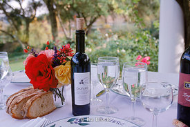 table setting of olive oil, bread, red wine, water
