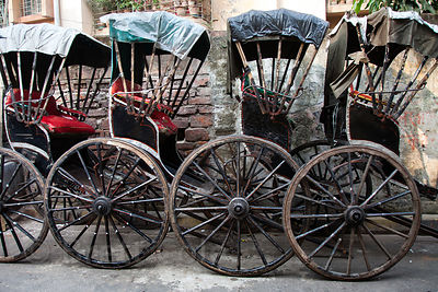 A row of weathered wooden rickshaws parket on a street in Shyambazar, Kolkata, India.