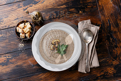 Mushroom soup with croutons on wooden table