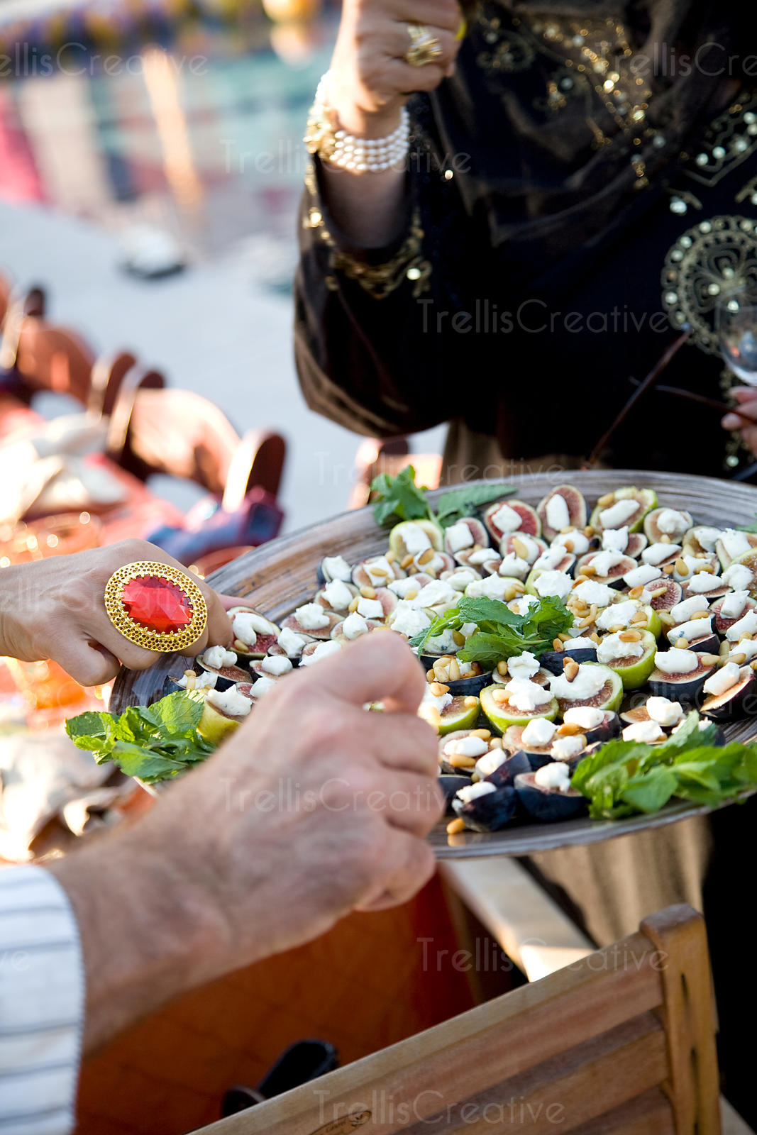 Guests eat figs with goat cheese at a sunset party