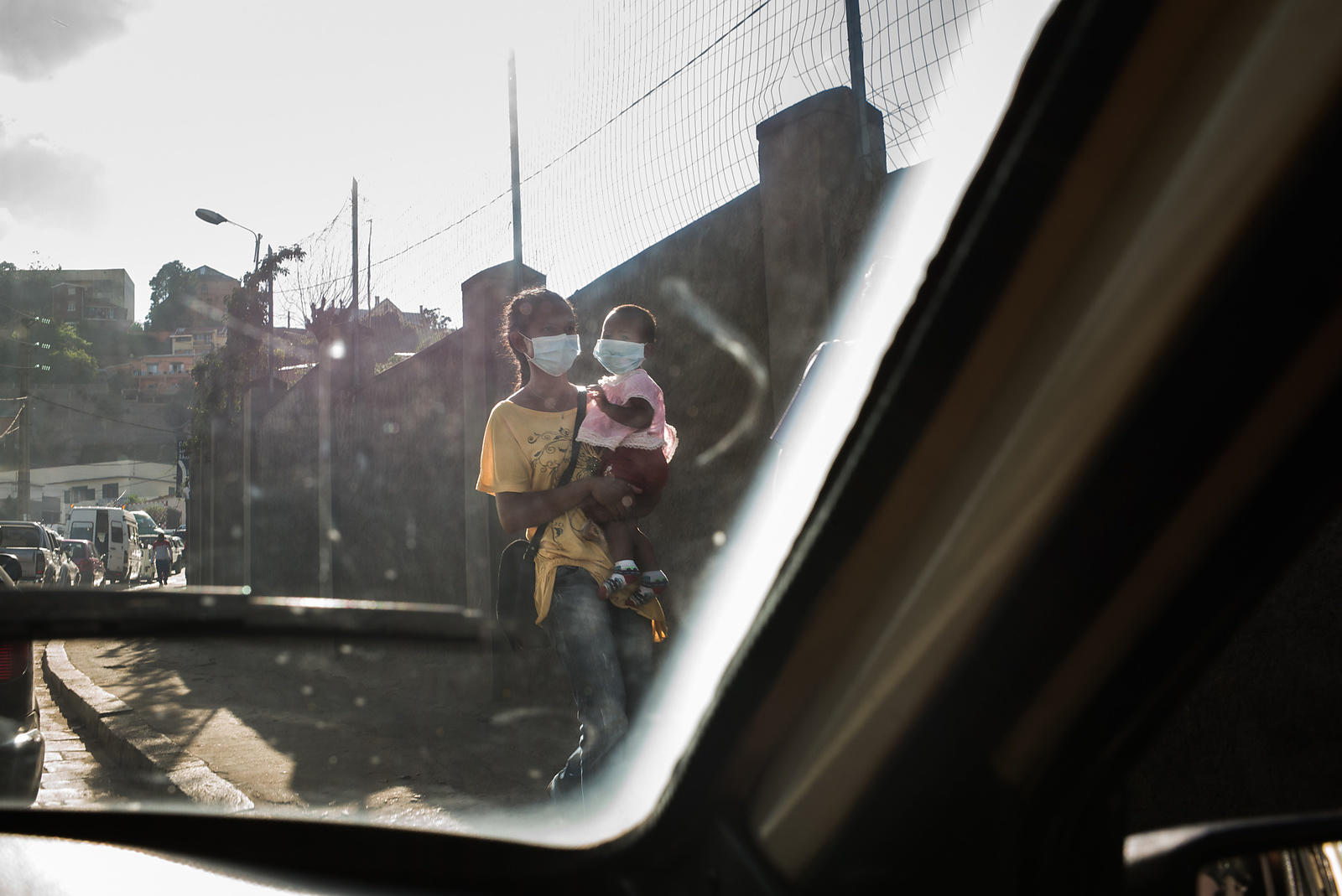 A woman and a baby wearing mask to protect themselves against possible infection of plague walk in Antananarivo on October 2, 2017.