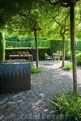 Gravelled courtyard area beside the studio with four weeping ash, Fraxinus excelsior 'Pendula' forming a shady canopy, steel and lead container, filled with an arrangement of stone setts and a seating area surrounded by yew hedging. Tony Ridler's Garden, Cockett, Swansea, UK
