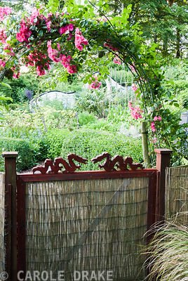 Gate into the kitchen garden is decorated with small carved dragons and framed with an arch of pink roses. Beggars Knoll, Newtown, Westbury, Wiltshire, BA13 3ED, UK
