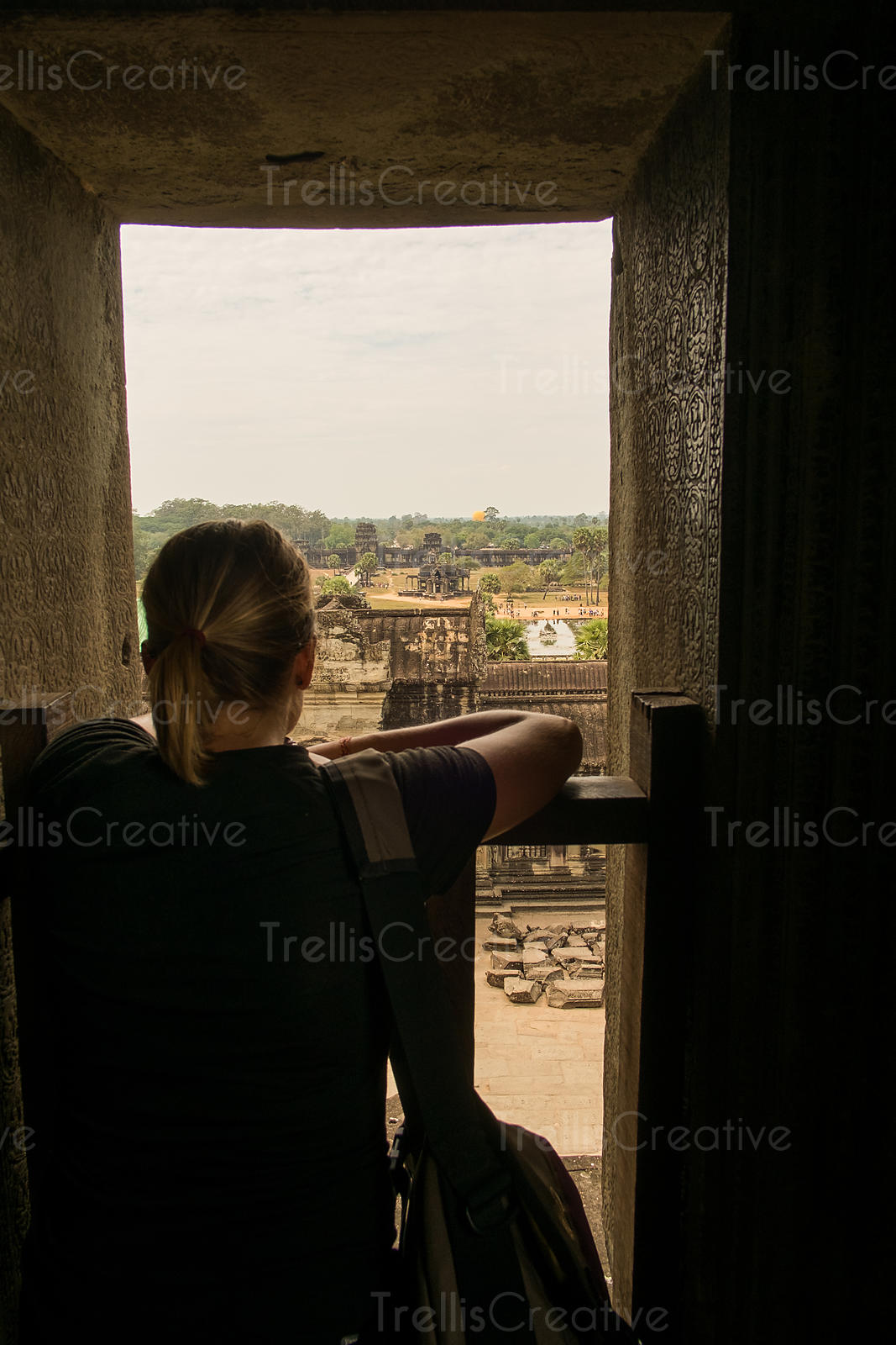 Female tourist looking out at the view of Angkor Wat from temple window