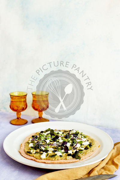 Red Lentil Flatbread with Roasted Poblano Tomatillo Pesto. Photographed on a lilac background.