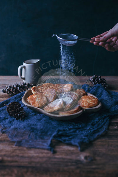 Woman's hand dusting sweet fritters with powdered sugar
