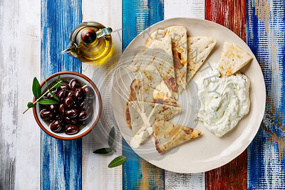 Yogurt dip with herbs Dzadziki cacik sauce, Pita bread, Olive oil and Olives on wooden background