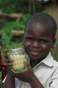 Young boy in green top drinking goats milk from glass,  Bunyole, eastern Uganda Africa