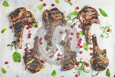 Grilled lamb ribs with pomegranate seeds, fresh mint and rosemary over metal baking tray background