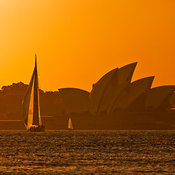 Sailboat and skyline at dusk in Sydney Harbor National Park, Mosman, New South Wales, Australia