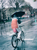 Man cycling on street with umbrella in rain