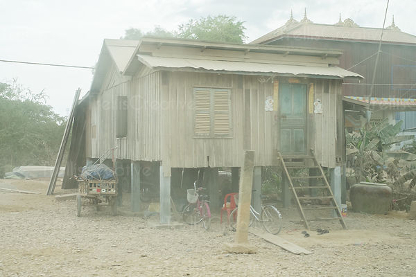 An old wooden stilt house along a dusty road in Cambodia