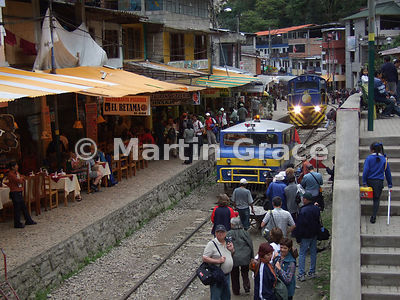 The railway line street in Aguas Calientes, Peru, with tourists, locals, restaurants and two trains