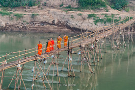Monks crossing a bamboo bridge over the Nam Khan River near the confluence with the Mekong River in Laos.