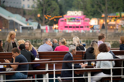 People eating and drinking at an outdoor restaurant with London's Southbank in the background