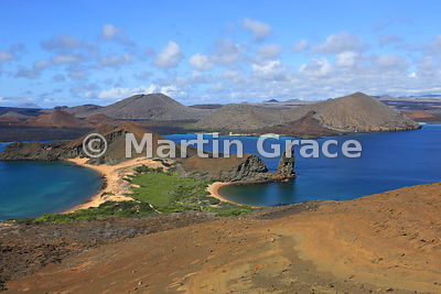 Classic view from the summit viewpoint of Bartolome Island across the western tip of Bartolome and Sullivan Bay to the lava flows, cinder cones and tuff cones of Santiago, Galapagos Islands