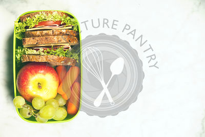 Green school lunch box with sandwich, apple, grape and carrot close up on white background. Healthy eating habits concept.