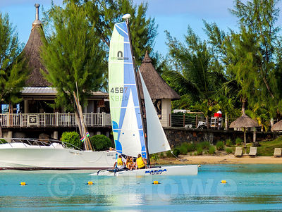 Mini Catamaran Sailing past Straw Roofed Buildings in Mauritius Resort