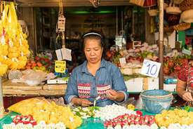 A woman selling flowers at Pak Khlong Market (Flower Market) in Bangkok, Thailand.
