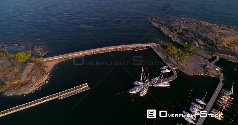 Concrete bridge, aerial view above a harbor full of yachts and sailboats and towards a bridge connecting two islands, on a sunny summer evening dusk, Helsinki, Uusimaa, Finland