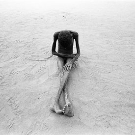 A young girl driven mad by hunger, sits playing in the sand. Ajiep, South Sudan