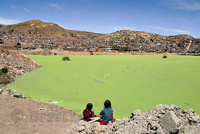 Children play at the banks of Lake Titicaca in Puno, Peru. Pollution from this rapidly growing city has fouled the shores, giving rise to a thick covering of algae.