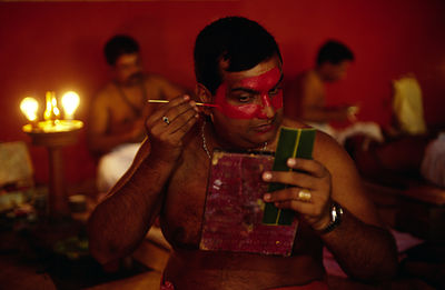 India - Kerala - An actor applies his make up before a performance at the Kerala Kalamandalam.
