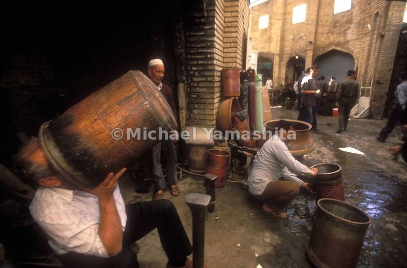 In a market in Baghdad, copper pots being repaired are beaten and soldered on small anvils stuck in the ground.