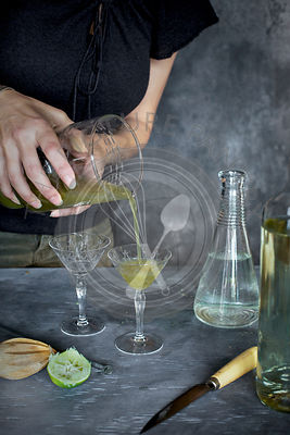 A women is preparing a matcha wine cocktail.
