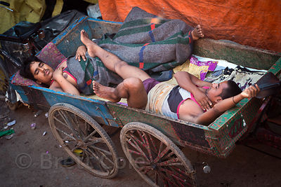 Two homeless men lie sleeping in a wooden cart in Chandni Chowk, Delhi, India
