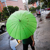 Women walking with green umbrella on Roxas Blvd, Manila, Philippines