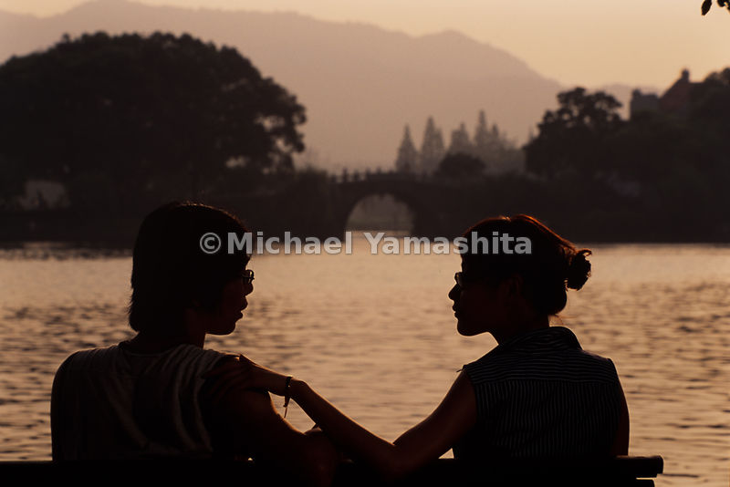 A young couple enjoys the lake and view of Rainbow bridge on West Lake in Hangzhou, China.