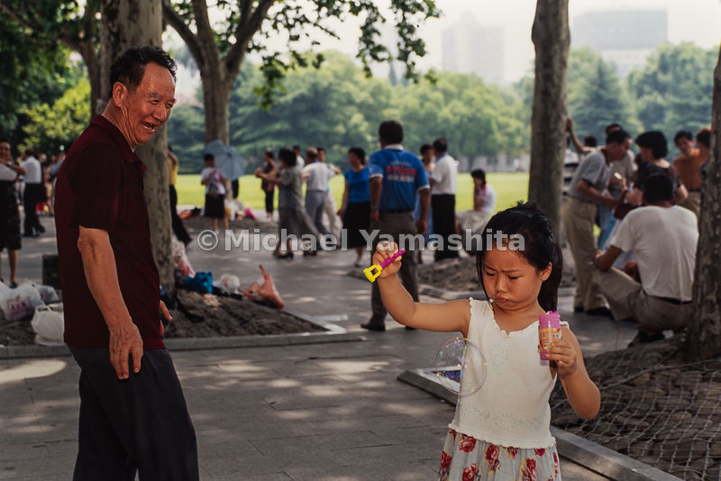 A girl makes bubbles in the park (no caption/location information)