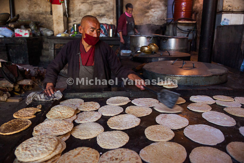 A monk in Gandze prepares the traditional flatbread of Central Tibet, called Balep Korkun. It is cooked on a griddle and made with barley flour, water and baking powder.