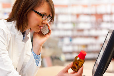 Pharmacist talking on phone at counter