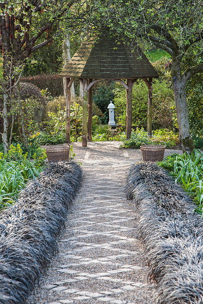 A path of stone setts and gravel in the Canal Garden is framed by black Ophiopogon planiscapus 'Nigrescens' and leads towards the Dell Garden with white drinking fountain as focal point. York Gate Garden, Adel, Leeds, Yorkshire