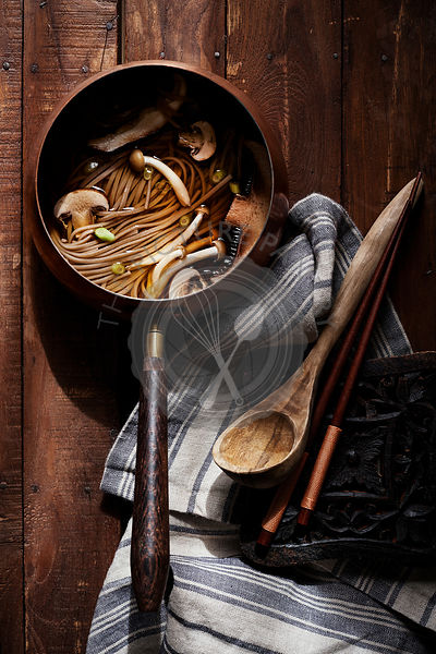 Old world copper pot filled with asian noodle soup and mushrooms on rich wood surface with antique wood spoon, linen and chopsticks.