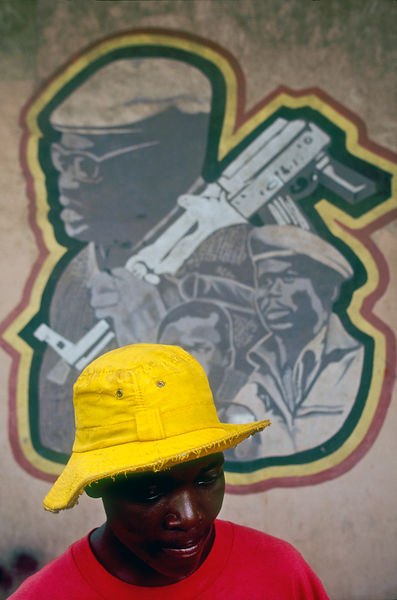 Angola - Luanda - A street boy stands in front of a poster of Agostinho Neto