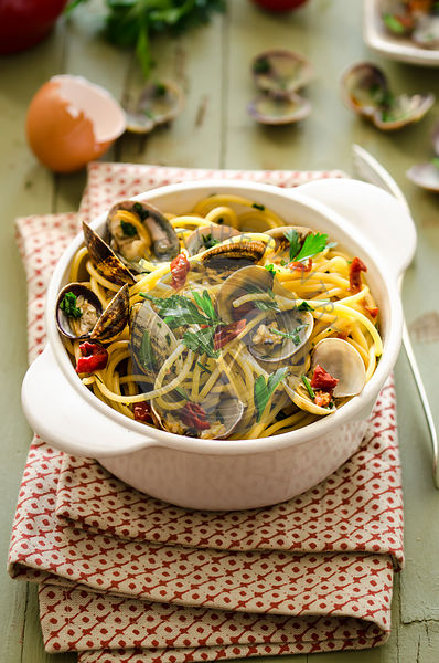 Spaghetti with clams, dried tomatoes, spicy salami and parsley