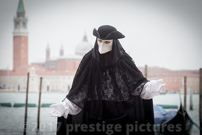 Man dressed as Venetian Nobleman wearing a Bauta Cera Mask by the Lagoon in Venice