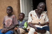 Kenyan woman reading Holy Bible to her family. Kenya.