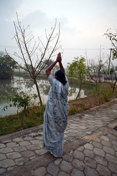 India - Cuddalore - A resident makes a salutation to the sun at dawn