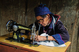 Black Hmong Woman using Sewing Machine