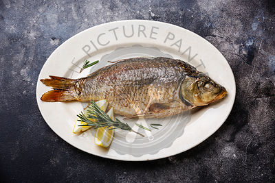 Baked carp roasted with lemon on plate