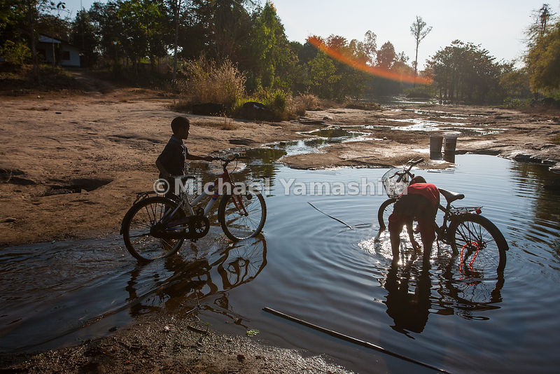 Home stay village. Kids wash their bikes in stream that runs thru the village.