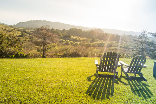 Wooden Adirondack chairs on green grass overlooking a beautiful landscape